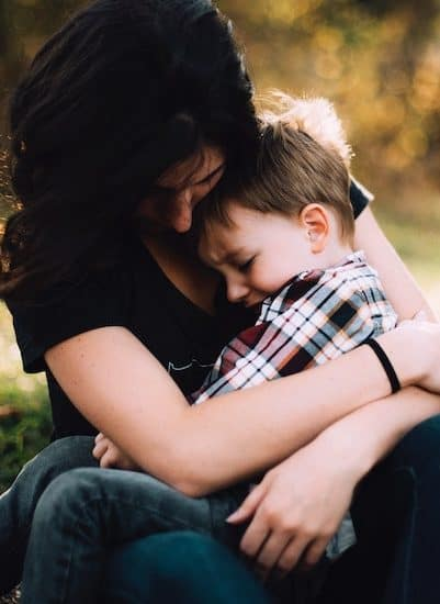 mother hugging sad little boy while solo parenting