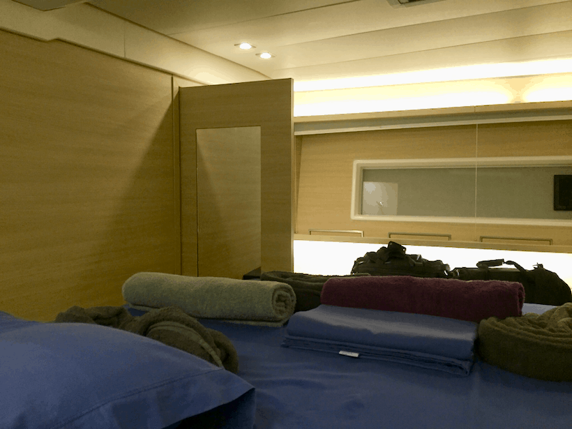Small cabin with blue bedspread, towels, and two black duffel bags onboard a yacht
