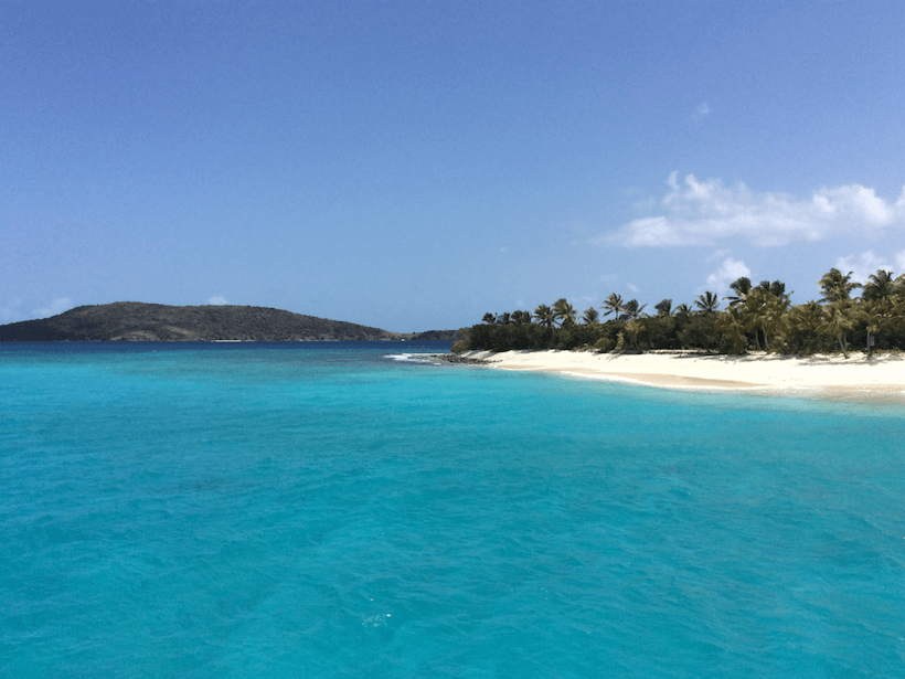 yacht parked next to a white sand beach with turquoise water