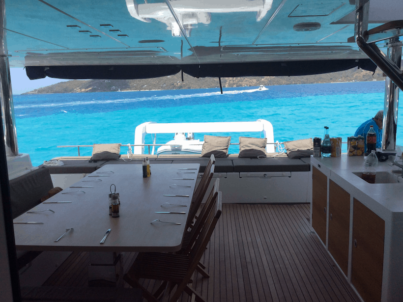 A large dining table aboard a yacht with turquoise water in the background