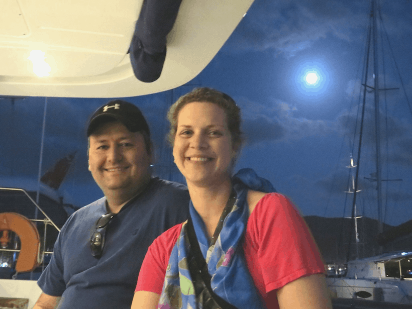 Couple on a yacht with the full moon in the distance