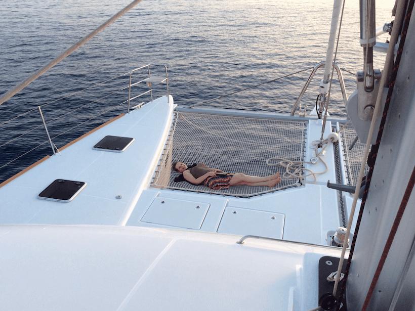 Woman in a hammock aboard a yacht.