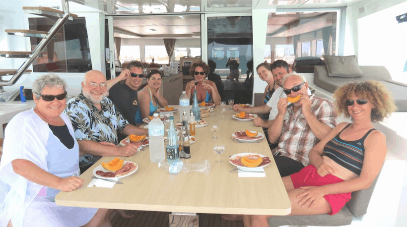 9 people sitting at a large dining table onboard a yacht