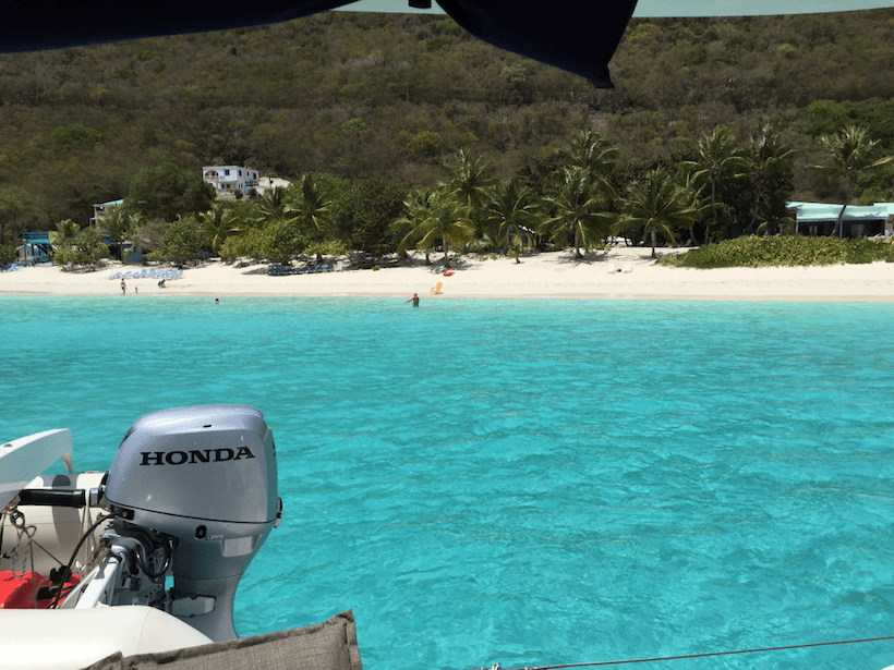 tender boat attached to yacht with turquoise water and beach at Jost van Dyke in the distance