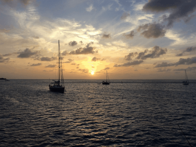 Yachts in the distance on the water at sunset