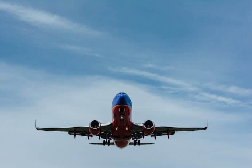 Blue and red airplane flying in blue sky
