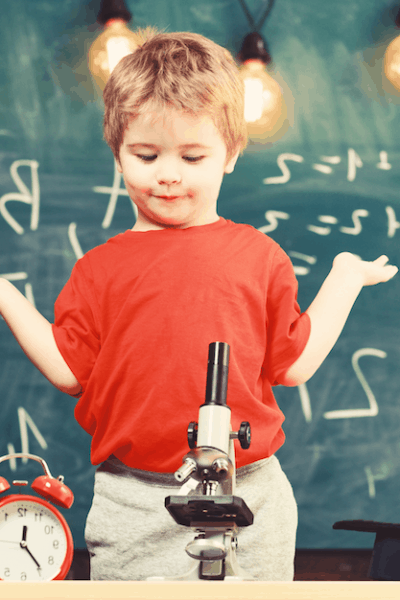 Child in red shirt shrugging shoulders in homeschool room with microscope and blackboard