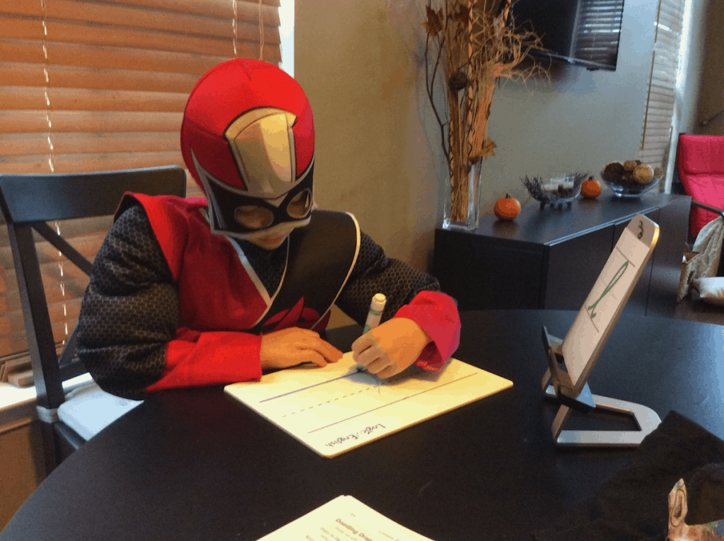 Boy in a power ranger costume sitting at the table doing a homeschool lesson