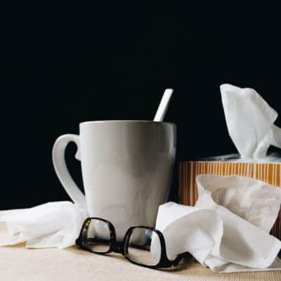 grey mug, tissues, and glasses on table