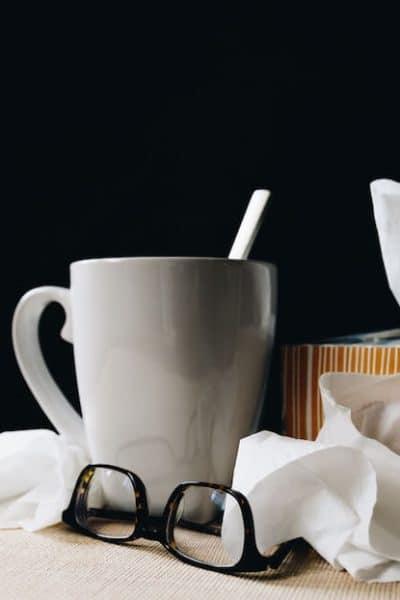 grey mug, tissues, and glasses on table