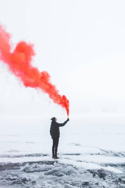 Person standing on snow in black winter clothing and releasing red smoke into sky