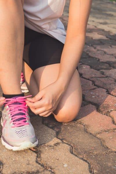 Woman tying running shoes