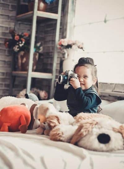 photo of girl on bed with camera and stuffed animals