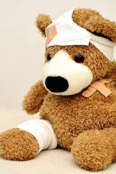 stuffed bear post surgery with white bandages and band-aids