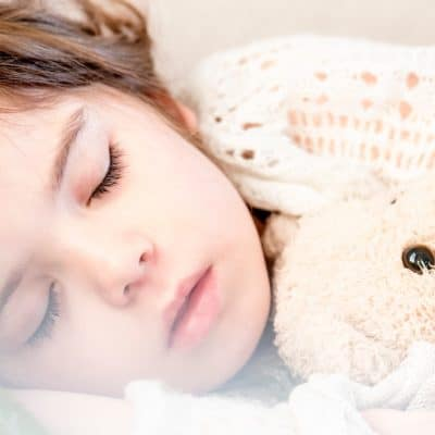sleeping kid with teddy bear and stomach flu