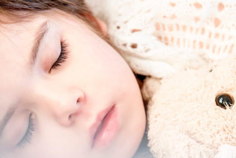 sleeping kid with teddy bear and stomach flu